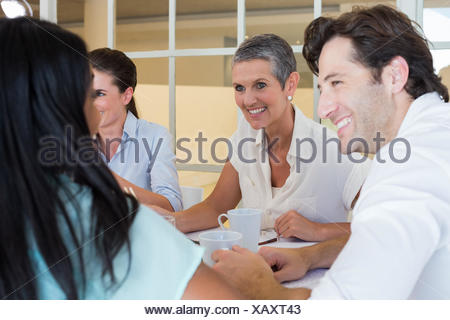 Business people smile and chat while enjoying hot drinks - Stock Photo