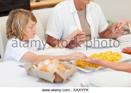 Family saying a prayer before dinner - Stock Photo