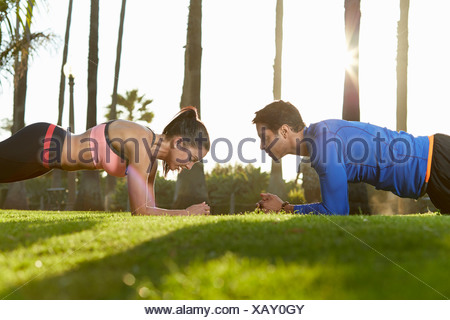 Man and woman doing plank exercise - Stock Photo