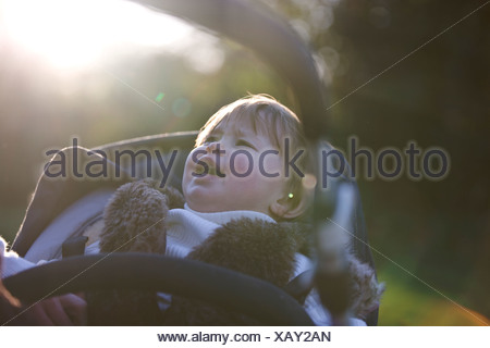 A baby girl crying in her stroller - Stock Photo