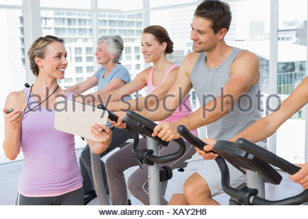 Trainer besides people working out at spinning class - Stock Photo