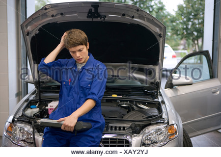 Female mechanic looking at diagnostic computer by open bonnet of car, hand to head - Stock Photo