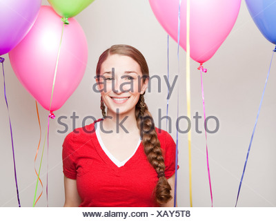 Studio Shot of young woman holding balloons - Stock Photo