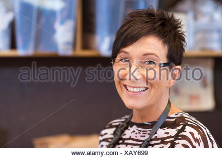 Portrait of smiling mature seamstress in workshop - Stock Photo