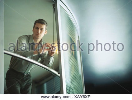Businessman leaning on rail, low angle view - Stock Photo