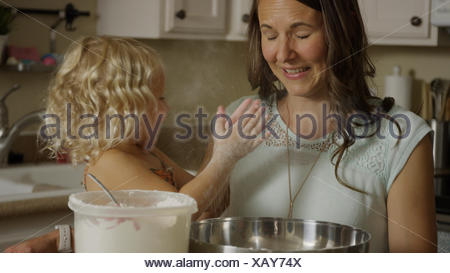 Mother and daughter playing with flour and learning to bake in kitchen - Stock Photo