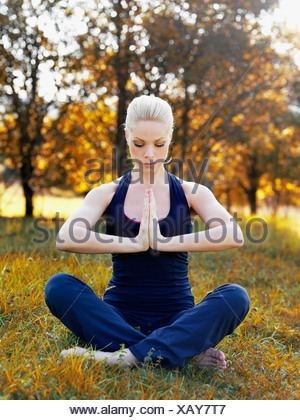 A woman practicing yoga in nature - Stock Photo