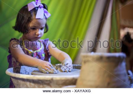 Little girl learning to work with potter's wheel. Selective focus. - Stock Photo