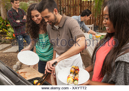 Friends sitting around table sharing barbecue food - Stock Photo