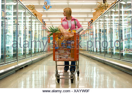 Woman grocery shopping in frozen foods section - Stock Photo