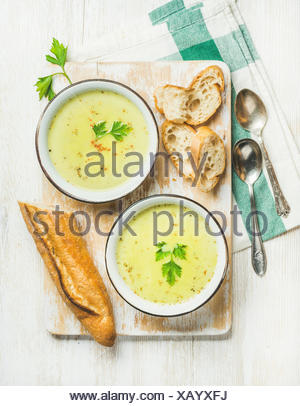 Green vegetable soup with parsley and baguette on white shabby wooden board over white painted wooden background, top view, vert - Stock Photo