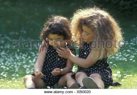 little girl consoling her sister in garden - Stock Photo