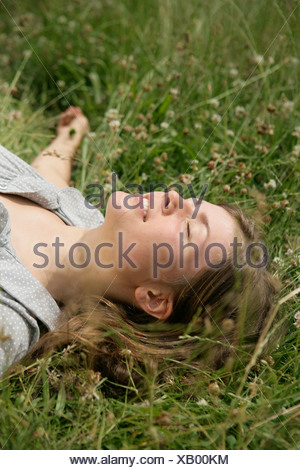 Close up of young woman lying in grass with eyes closed - Stock Photo