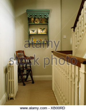 Small green shelves on wall above child's antique high chair on traditional cream landing - Stock Photo