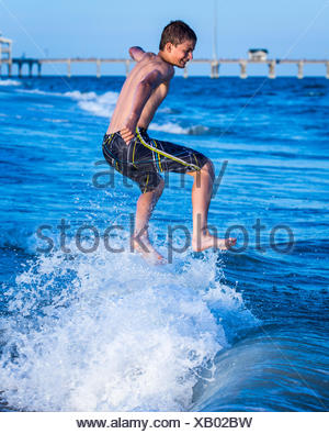 Boy jumping in the ocean surf - Stock Photo