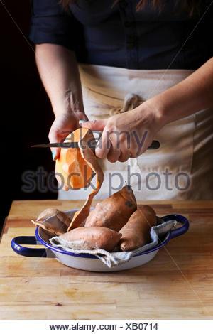 Female peeling orange sweet potatoes. - Stock Photo