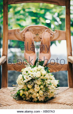 Wedding bouquet and bride's shoes on a chair - Stock Photo