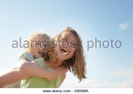 Low angle view of girl giving sister piggy back at coast - Stock Photo