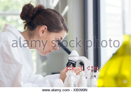 Portrait of young female chemist looking through microscope - Stock Photo