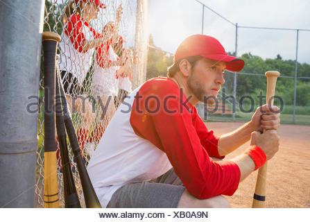 Baseball player holding bat on field - Stock Photo