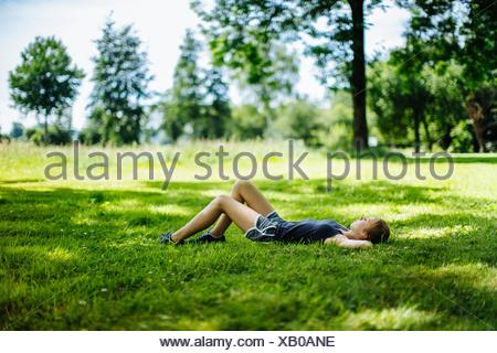 Young girl in park, lying on grass, relaxing - Stock Photo