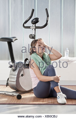 Woman wiping sweat by exercise machine - Stock Photo