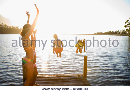 Family standing on jetty children 7 10 jumping into lake rear view lens flare backlit - Stock Photo