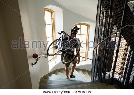 Sweden, Cyclist carrying bicycle on steps - Stock Photo