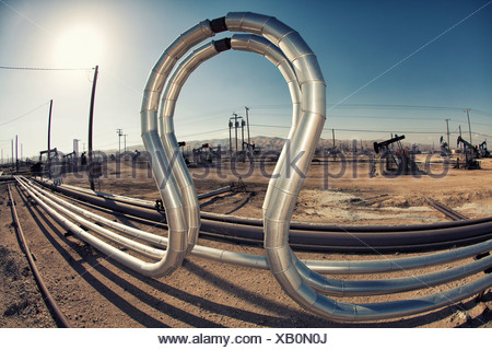 Curved pipes in oil field - Stock Photo