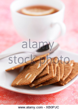 Cinnamon and thinly sliced almond cookies, a cup of coffee - Stock Photo