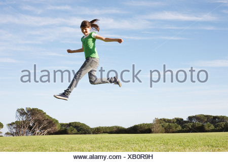 Girl jumping in mid-air - Stock Photo