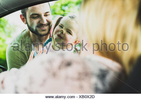 Girl with father looking at mother in car - Stock Photo