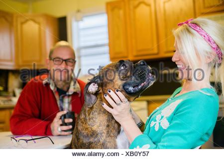 Young woman smiling at boxer dog, face to face - Stock Photo