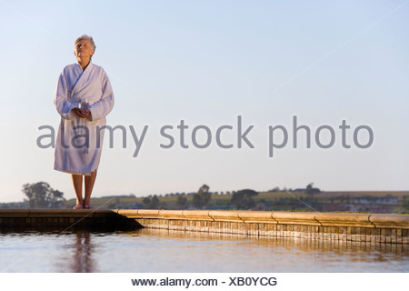 Senior woman wearing white bath robe, standing outdoors by swimming pool, eyes closed - Stock Photo