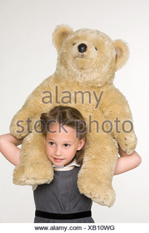 A girl shoulder carrying a tedy bear - Stock Photo