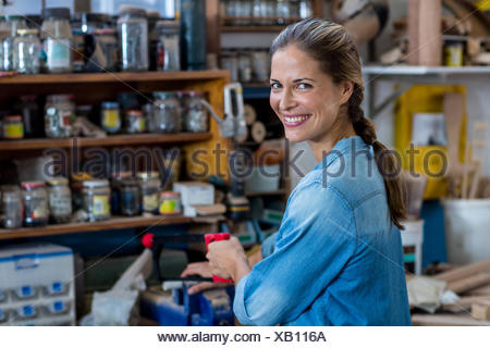 Female carpenter using coping saw to cut the piece of wood - Stock Photo
