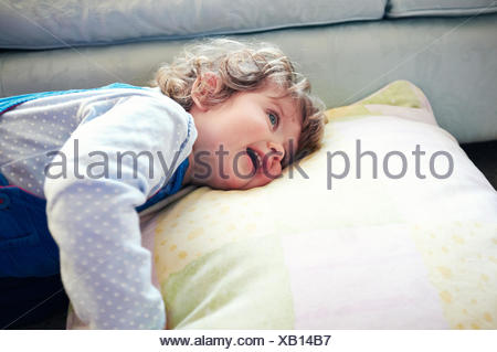 Girl laying on pillow in living room - Stock Photo