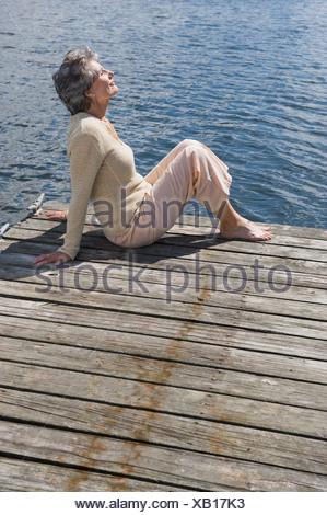 Senior woman sitting on dock - Stock Photo