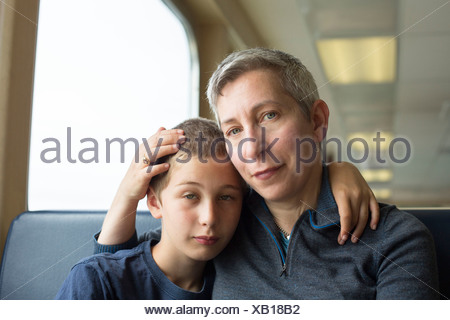 Mother and son sitting together with arm around - Stock Photo