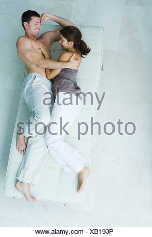 Couple lying on chaise longue together, woman's hand on man's bare chest, full length, view from above - Stock Photo