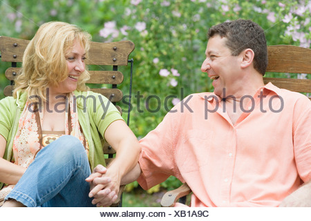 Mature couple sitting on chairs and holding each other's hands - Stock Photo