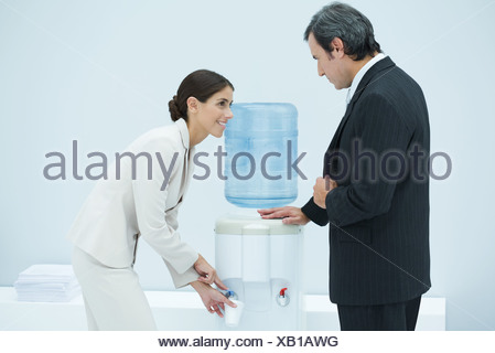 Two professionals chatting beside water cooler, woman filling disposable cup - Stock Photo