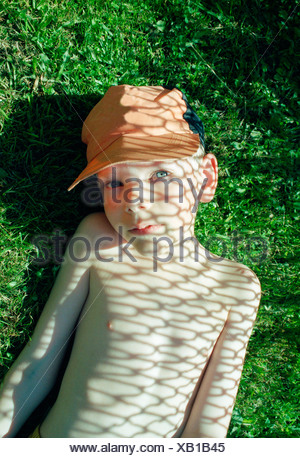 Boy laying in shadow of chain link fence - Stock Photo