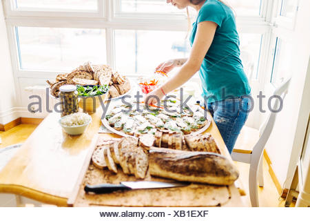 Side view of woman preparing open faced sandwich at table - Stock Photo