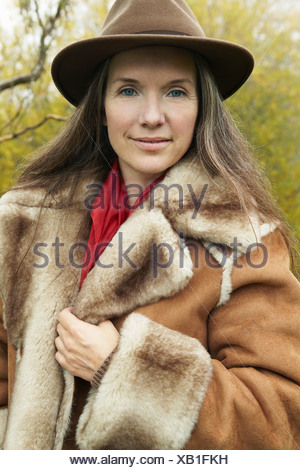 Older woman wearing fur lined coat - Stock Photo
