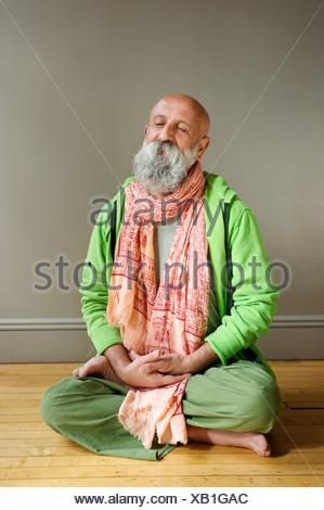 Portrait of senior man sitting in lotus position on floor - Stock Photo