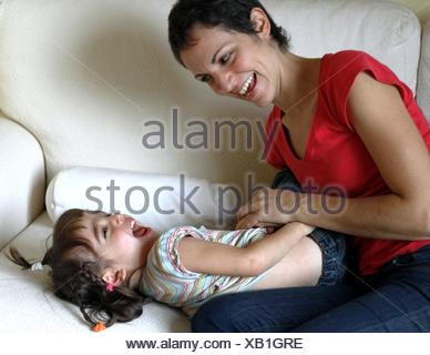 Mother sitting on sofa tickling her daughter - Stock Photo
