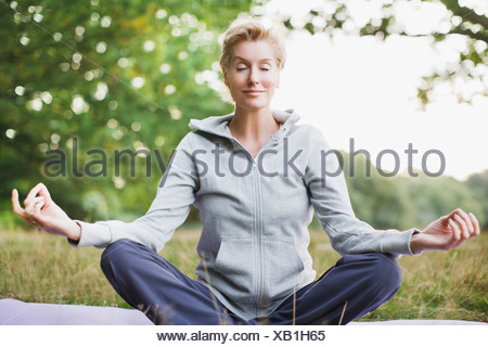 Tranquil woman practicing yoga - Stock Photo