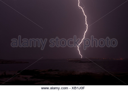 Scenic shot of lightning storm over the peaceful sea in the evening - Stock Photo