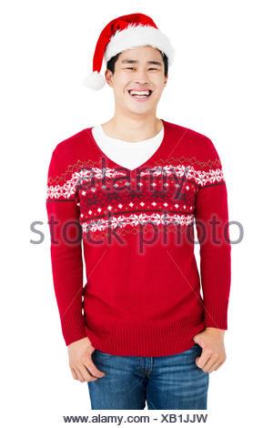 Young man wearing santa hat looking at camera and smiling - Stock Photo